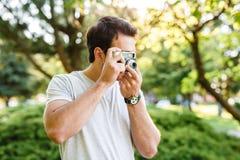 Stilig man som tar foto med den parallella kameran Royaltyfri Fotografi