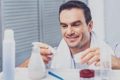 Stilig man som tar raka kräm- anseende i badrum fotografering för bildbyråer