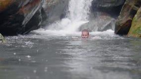 Stilig man som tycker om bad i bergfloden från den tropiska vattenfallet i den unga mannen för rainforest som badar i den steniga arkivfilmer