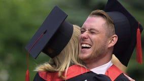 Stilig man som uppriktigt ler och att omfamna den kvinnliga vännen, avläggande av examenceremoni stock video
