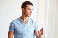 Stilig man som ut ser fönstret Fotografering för Bildbyråer