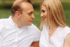 Stilig manblick på hans härliga kvinna Sitter det attraktiva paret för den nära övre sikten på bänken i parkerar Man för blont hå royaltyfria foton