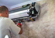 Stilig manelektriker som installerar att betinga för luft arkivbild