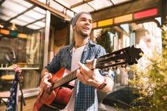 Stilig manlig gitarrist som bedrar med gitarrlek royaltyfri bild