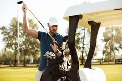 Stilig manlig golfare som tar klubbor från en påse i en golfvagn Royaltyfri Bild