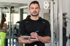 Stilig manlig instruktör With Clipboard In en idrottshall Arkivbilder