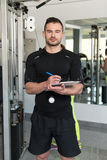 Stilig manlig instruktör With Clipboard In en idrottshall Fotografering för Bildbyråer