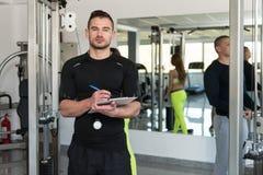Stilig manlig instruktör With Clipboard In en idrottshall Arkivbild