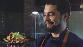 Stilig manlig kock som ler den hållande plattan med sallad lager videofilmer