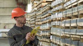Stilig manlig lagerarbetare som går handstil på hans skrivplatta stock video