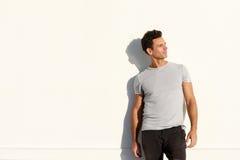 Stilig manlig modemodell i t-skjorta anseende mot den vita väggen fotografering för bildbyråer