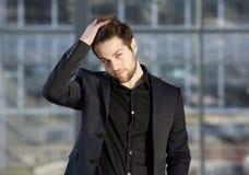 Stilig manlig modemodell som poserar med handen i hår arkivfoton