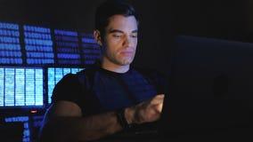 Stilig manlig programmerare som arbetar på en dator på natten i kontoret, fyllde med bildskärmskärmar lager videofilmer