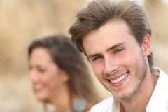 Stilig manstående med en perfekt vitt tand och leende royaltyfri foto