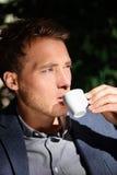 Stilig manstående som dricker espresso på kafét arkivbild