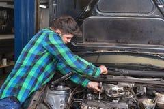 Stilig mekaniker som talar på telefonen, medan reparera en bil arkivfoto