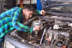 Stilig mekaniker som talar på telefonen, medan reparera en bil fotografering för bildbyråer