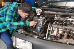 Stilig mekaniker som talar på telefonen, medan reparera en bil royaltyfria bilder