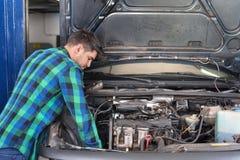 Stilig mekaniker som talar på telefonen, medan reparera en bil royaltyfri fotografi