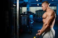Stilig muskulös kroppsbyggareman som gör övningar i idrottshall Royaltyfri Bild
