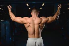 Stilig muskulös kroppsbyggareman som gör övningar i idrottshall Fotografering för Bildbyråer