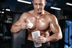 Stilig muskulös kroppsbyggareman som gör övningar i idrottshall Royaltyfri Foto