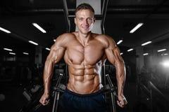 Stilig muskulös kroppsbyggareman som gör övningar i idrottshall Arkivbilder