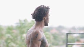 Stilig muskulös man med tatueringar på hans kala tillbaka moment ut på den öppna balkongen arkivfilmer