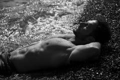 Stilig muskulös man på stranden som lägger på grus fotografering för bildbyråer
