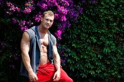 Stilig muskulös ung man utomhus med blommor bakom Royaltyfria Bilder