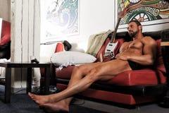 Stilig naken atletic mankroppsbyggare med lek för elektrisk gitarr royaltyfria bilder