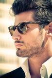 Stilig och attraktiv ung man som är utomhus- med solglasögon royaltyfria foton