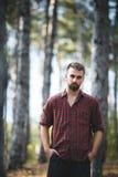 Stilig passformman som poserar i skogen som bär den kontrollerade skjortan Royaltyfri Fotografi