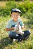 Stilig pojke för gullig bonde i jeans som tycker om sommardag i byliv med blommor som ler happyly med kaninkaninen i korg Royaltyfri Bild