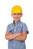 Stilig pojke i den blåa rutiga skjorta- och gulingbyggnadshjälmen som ler på vit bakgrund Fotografering för Bildbyråer