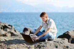 Stilig pojke med en bärbar dator Royaltyfri Foto
