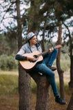 Stilig pojke som spelar begrepp för gitarrträdskog Arkivbild