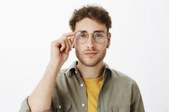 Stilig professor som är klar att lyssna Charmig flirty caucasian man med borstet i exponeringsglas, rörande kant av eyewearen och royaltyfri bild