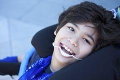 Stilig rörelsehindrad pojke, i att le för rullstol som ser upp Arkivbilder