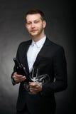 Stilig romantisk maninnehavflaska och exponeringsglas av vin Royaltyfri Bild