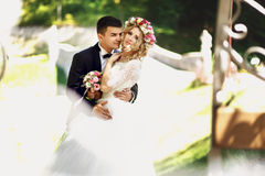 Stilig säker brudgum som kramar blond brudcarria för vit klänning Arkivfoto