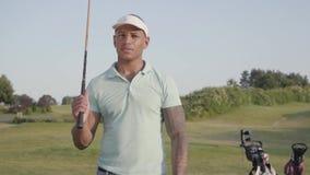Stilig säker lyckad mitt - östlig man med ett golfklubbanseende på en golfbana i bra soligt väder sport arkivfilmer