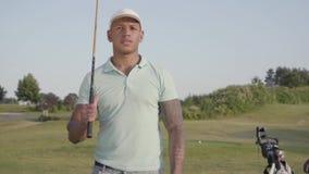 Stilig säker lyckad mitt för stående - östlig man med ett golfklubbanseende på en golfbana i bra soligt lager videofilmer