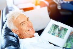 Stilig senniorman som läser en bok som kopplar av på en soffa royaltyfria bilder