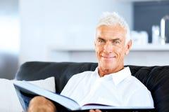 Stilig senniorman som läser en bok som kopplar av på en soffa royaltyfria foton