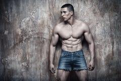 Stilig sexig muskulös man, abs, på väggbakgrund arkivbild