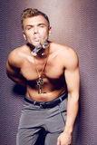Stilig sexig ung man med den nakna torson som röker en cigarr Arkivfoton