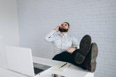Stilig skäggig affärsman som i regeringsställning arbetar med bärbara datorn och att kalla Arkivfoton