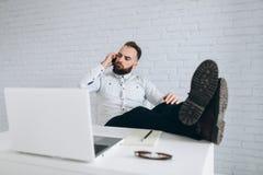 Stilig skäggig affärsman som i regeringsställning arbetar med bärbara datorn och att kalla Royaltyfria Bilder