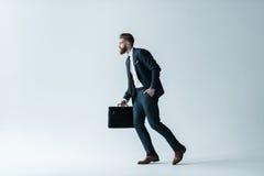 Stilig skäggig affärsmanspring med portföljen på grå färger Arkivfoton